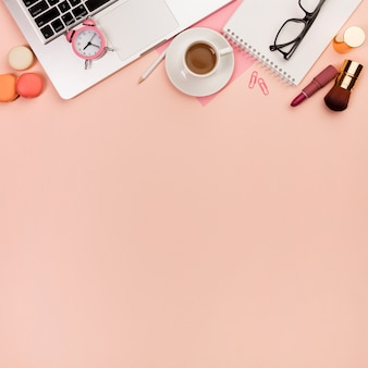 Macaroons, pincéis de maquiagem com despertador no laptop e artigos de papelaria no cenário de pêssego