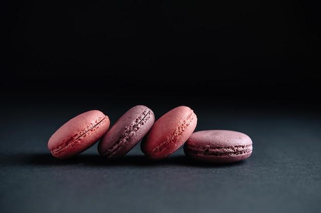 Macaroons rosa na parede escura