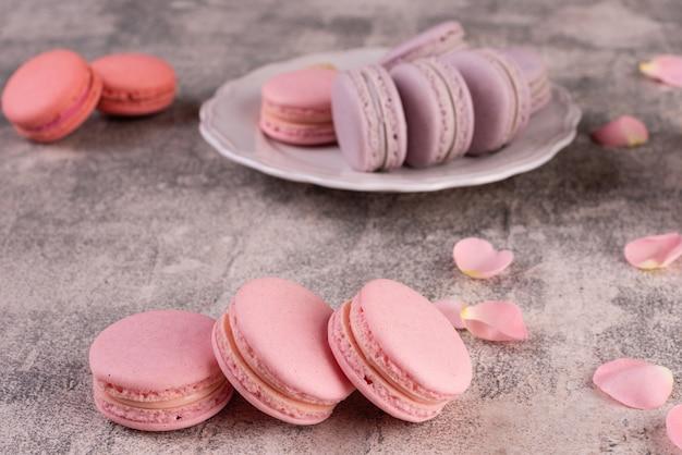 Macaroons saborosos rosa lindos sobre um fundo de concreto