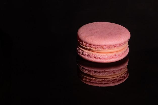 Macaroons saborosos rosa lindos sobre um fundo escuro