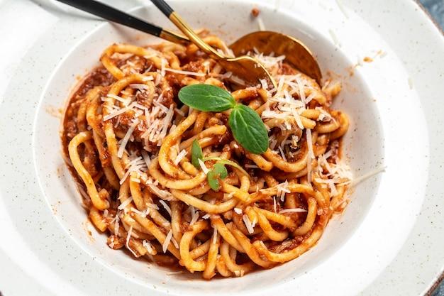 Macarrão à bolonhesa com molho de tomate e carne picada servido em prato com queijo parmesão. prato italiano tradicional.