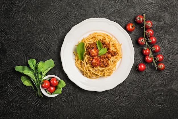 Macarrão à bolonhesa italiano clássico delicioso com tomates em um prato em um fundo escuro.