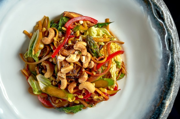 Macarrão agridoce com amendoim, legumes e cebola, servido em uma tigela branca.