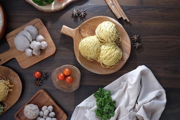 Macarrão amarelo cru com almôndegas e tomate na placa de madeira