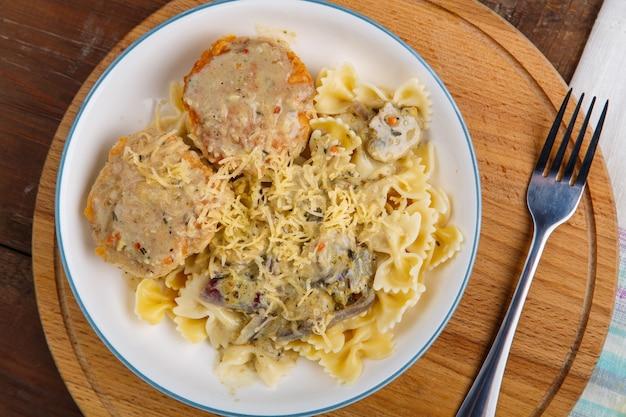 Macarrão ao molho cremoso com cogumelos e almôndegas de frango em um prato bege sobre uma mesa de madeira em um suporte redondo com um garfo