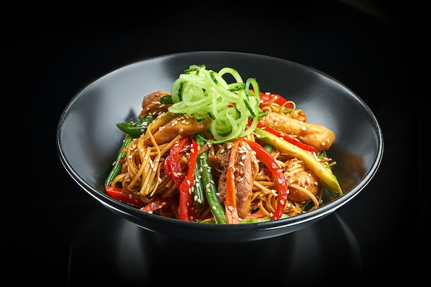 Macarrão apetitoso de ovo wok com frango, pimentão, aspargos, sementes de gergelim e pepino fresco em uma tigela preta sobre uma superfície preta com reflexão. comida de rua asiática