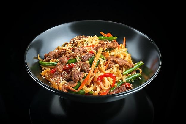 Macarrão apetitoso udon wok com carne, pimentão, aspargos, sementes de gergelim em uma tigela preta sobre uma superfície preta com reflexão. comida de rua asiática