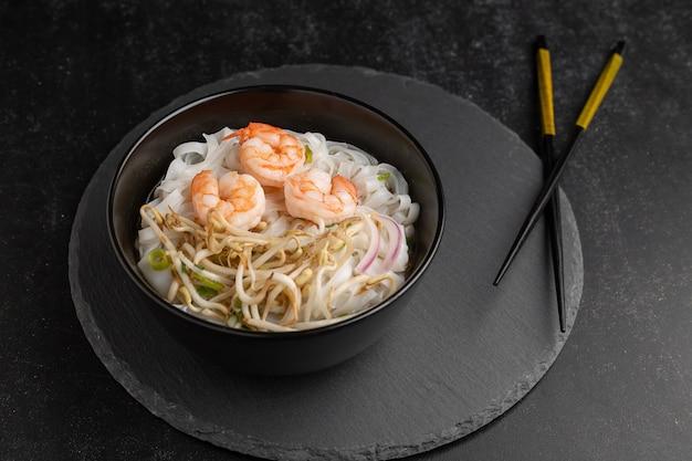 Macarrão asiático com camarão e frutos do mar em tigela preta