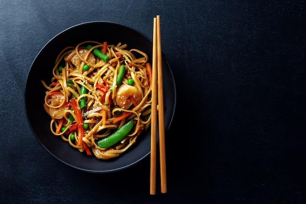 Macarrão asiático com camarão e legumes servidos em uma tigela em fundo escuro.