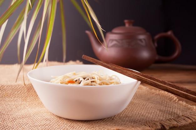 Macarrão asiático com carne, legumes na tigela com pauzinhos, fundo de madeira rústico. jantar de estilo asiático. macarrão japonês chinês