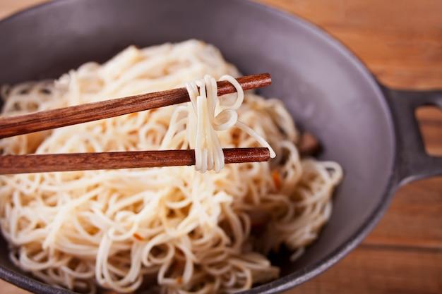 Macarrão asiático com carne, legumes no wok com pauzinhos, fundo de madeira rústico. jantar de estilo asiático. macarrão japonês chinês