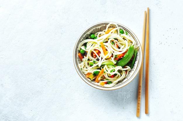 Macarrão asiático com legumes e gergelim servido em uma tigela.