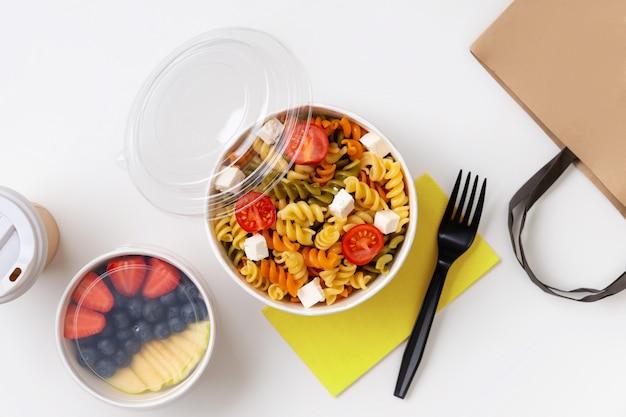 Macarrão, café e frutas em tirar caixas na mesa branca.