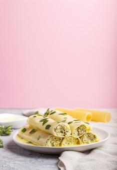 Macarrão canelone com molho de ovo, queijo creme e folhas de orégano.