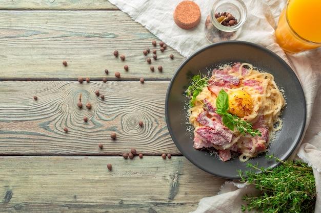 Macarrão carbonara. espaguete com bacon, parsel e queijo parmesão