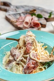 Macarrão carbonara, espaguete com macarrão bacon, queijo parmesão e molho cremoso. massa italiana. conceito de cozinha, imagem vertical. copie o espaço.