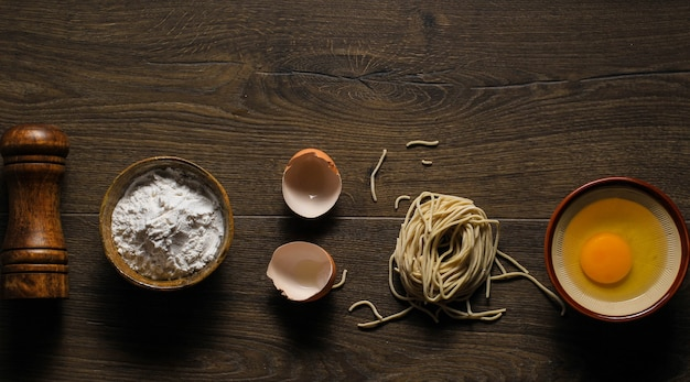 Macarrão caseiro asiático cru com ovos, sal, casca de ovo e farinha, espaço de cópia para papel de parede ou fundos