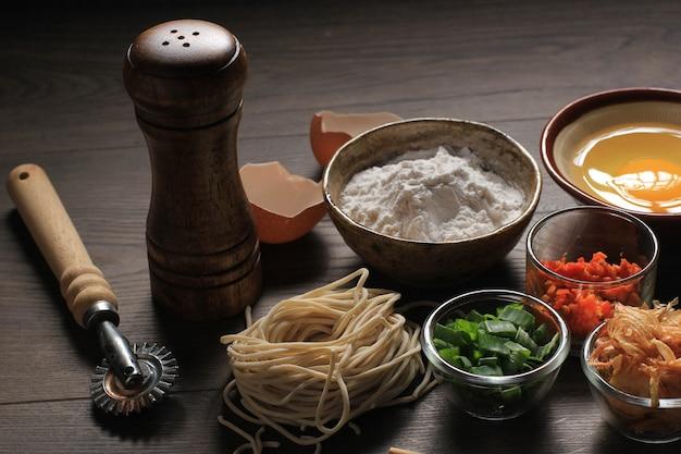 Macarrão caseiro asiático cru com ovos, sal, casca de ovo, pimenta picada, chalotas fritas e farinha, espaço de cópia para papel de parede ou fundos