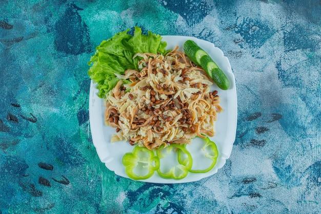 Macarrão caseiro com fatia de pimenta em um prato, na mesa azul.