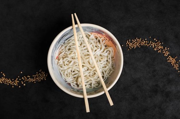 Macarrão caseiro de udon de comida japonesa com design de sementes de coentro em fundo preto