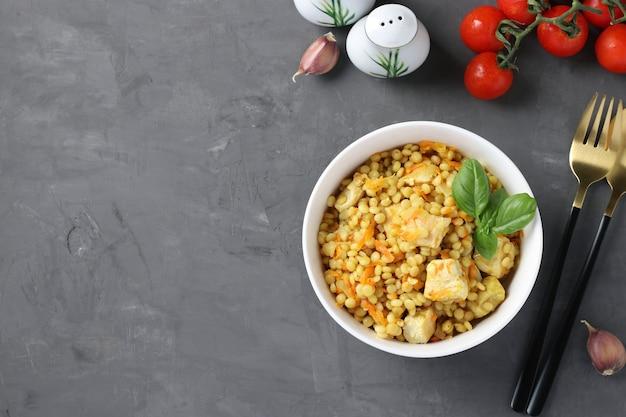 Macarrão caseiro ptitim com frango e legumes na mesa cinza escura. vista de cima. espaço para texto.