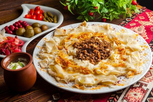 Macarrão caucasiano de guru khingal azerbaijano de vista lateral com carne picada frita e cebola com molho de creme de leite e picles em uma toalha de mesa em uma mesa de madeira escura horizontal