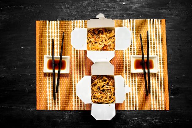 Macarrão chinês com camarão e molho de soja na bandeja de bambu