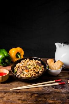 Macarrão chinês com carne e legumes, servido com rolinhos primavera na mesa de madeira
