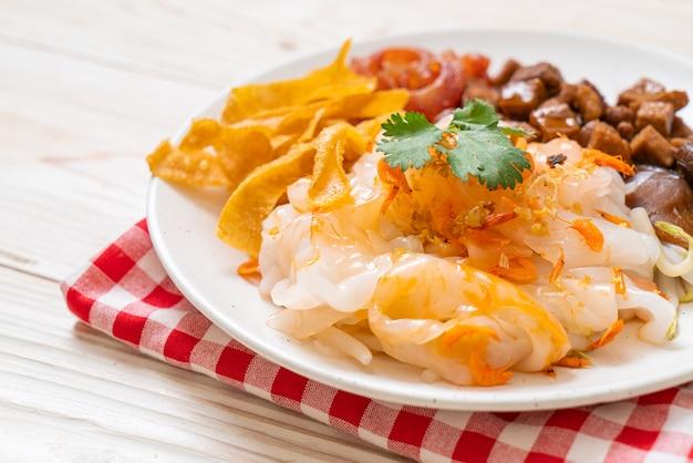 Macarrão chinês de arroz cozido no vapor com carne de porco e tofu em molho de soja doce - comida asiática