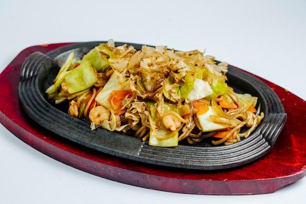 Macarrão chinês de camarão salteado com repolho e cenoura em panela de ferro fundido