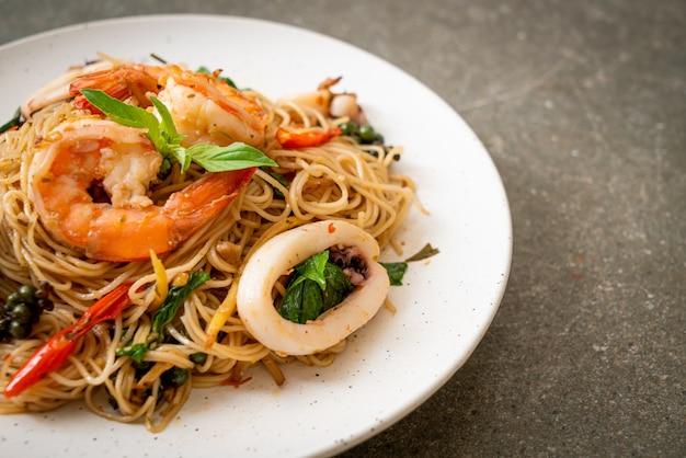 Macarrão chinês frito com manjericão, pimenta, camarão e lula - comida asiática