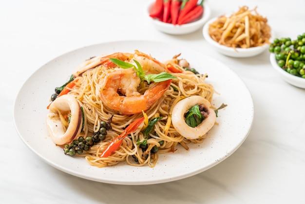 Macarrão chinês frito com manjericão, pimenta, camarão e lula, estilo de comida asiática