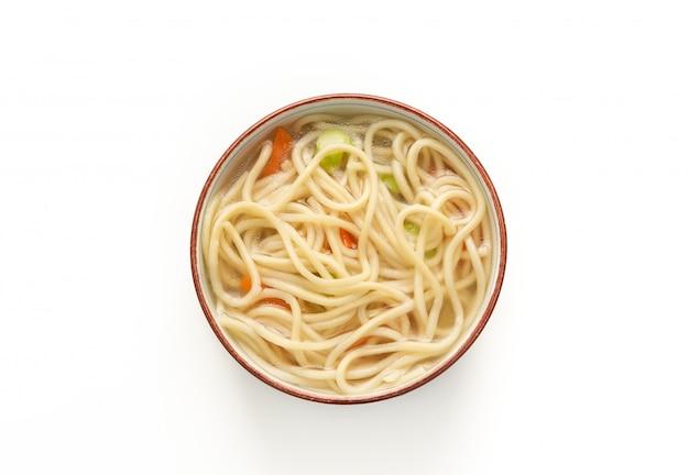 Macarrão chinês ou udon com legumes e pauzinho no branco isolado