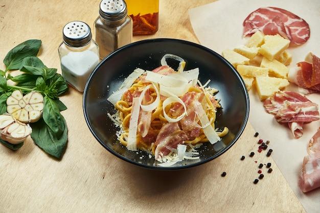 Macarrão clássico, caseiro de carbonara, com molho bechamel, bacon e parmesão em uma tigela preta. cozinha italiana tradicional