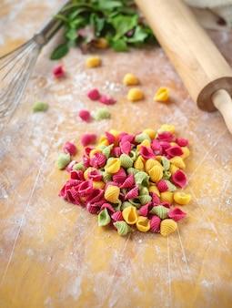Macarrão colorido cru na mesa de madeira na cozinha