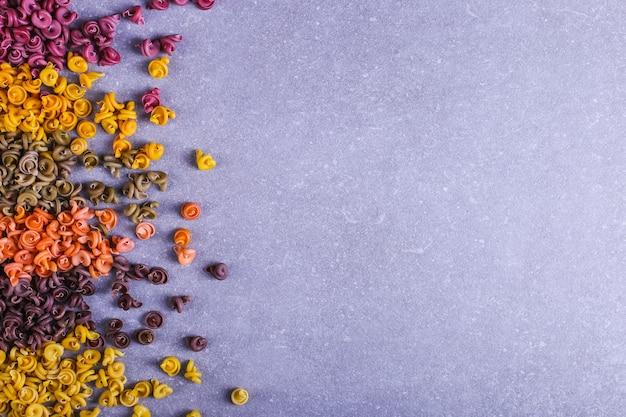 Macarrão colorido de forma incomum com corantes vegetais naturais, espalhados sobre a mesa closeup de fundo.