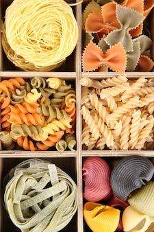 Macarrão colorido em caixa de madeira, close-up