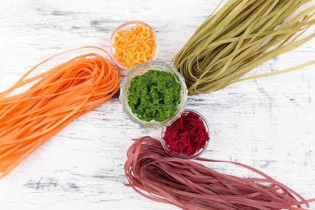 Macarrão colorido vegetal vegetariano com beterraba, cenoura e espinafre. ingrediente para preparar.