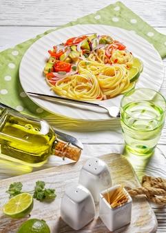 Macarrão com abacate, tomate e limão polvilhado com pimenta picada e cebola roxa em um prato branco sobre uma mesa de madeira servido com um copo de água, vista vertical de cima
