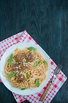 Macarrão com almôndegas e salsa em molho de tomate. mesa de jantar. menu de fundo da tabela. fundo de madeira escuro. vista do topo. espaço para texto.
