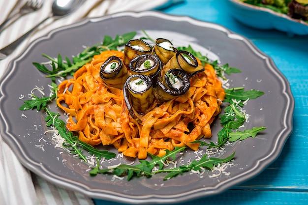 Macarrão com berinjela, tomate, queijo e rúcula. a apresentação original do prato do chef. sobre um fundo azul de madeira.