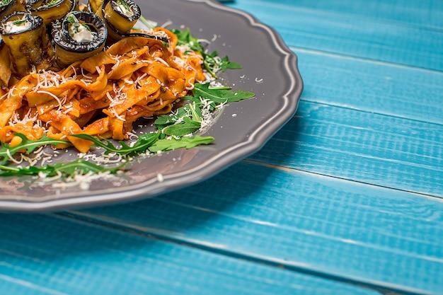 Macarrão com berinjela, tomate, queijo e rúcula