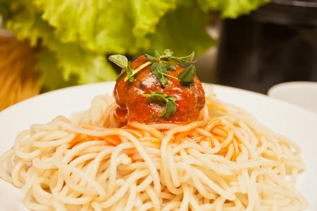 Macarrão com bolas de carne em molho de tomate no prato branco com legumes frescos na superfície.