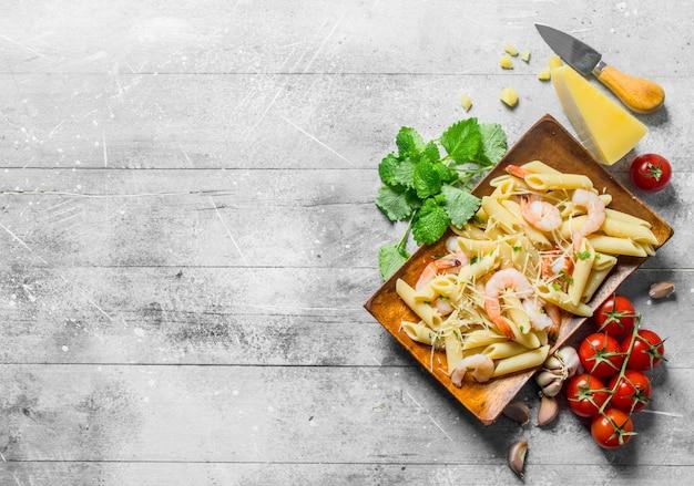 Macarrão com camarão, parmesão e cereja. em fundo branco de madeira