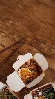 Macarrão com carne de porco e legumes em uma caixa para viagem na mesa de madeira. entrega de comida asiática. alimentos em embalagens de papel com fundo de madeira. foto vertical