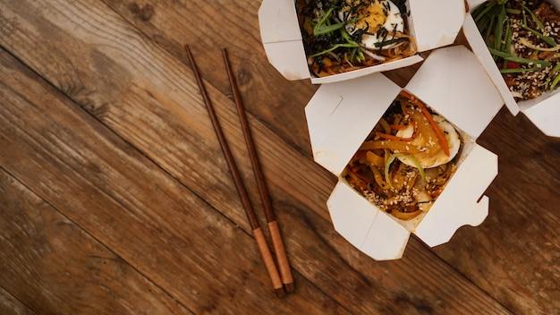 Macarrão com carne de porco e legumes em uma caixa para viagem na mesa de madeira. entrega de comida asiática. alimentos em embalagens de papel com fundo de madeira