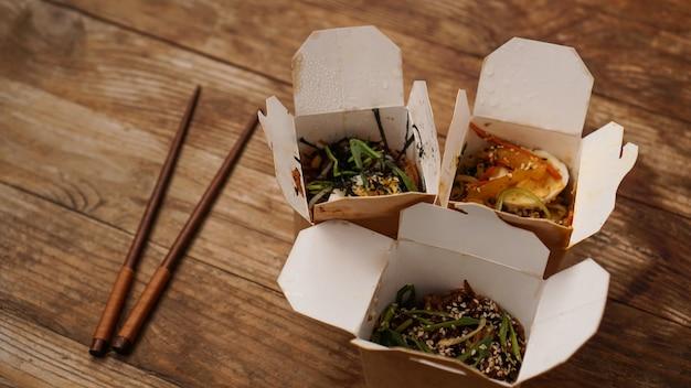 Macarrão com carne de porco e legumes em uma caixa para viagem na mesa de madeira. entrega de comida asiática. alimentos em embalagens de papel na mesa de madeira
