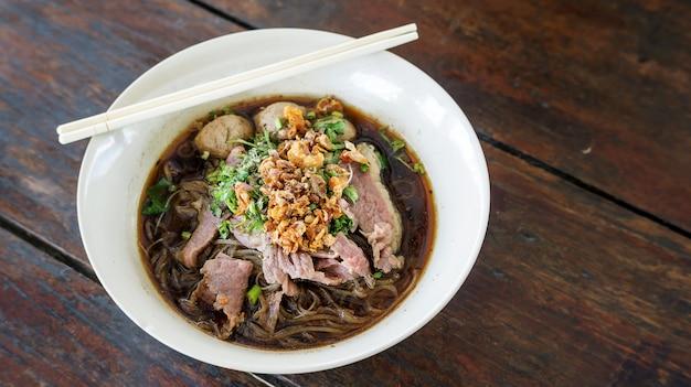 Macarrão com carne de porco em um fundo de madeira (macarronetes tailandeses).