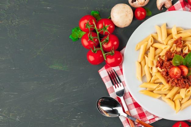 Macarrão com carne, molho de tomate e legumes em cima da mesa