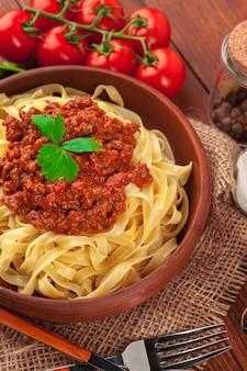 Macarrão com carne, molho de tomate e legumes na mesa